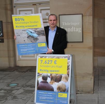 Jens Panse mit Plakatmotiven vor dem Landtag